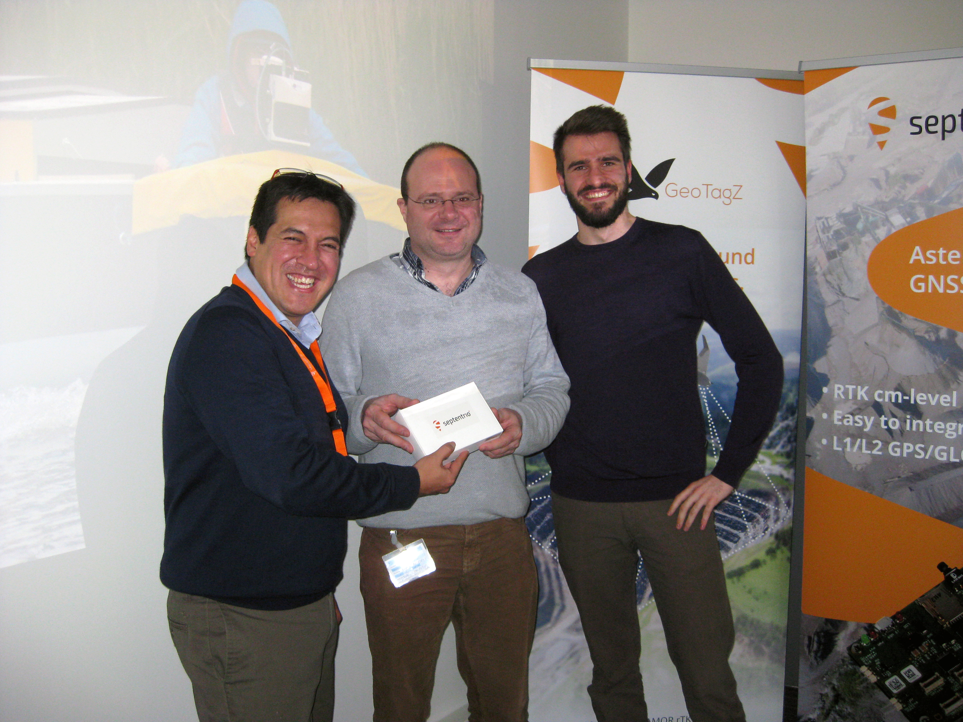 Gustavo Lopez, Product Manager at Septentrio presenting Dr. Geert Waeyenbergh, KU Leuven and  Gerben Peeters of the KU Leuven Ecochallenge team with the AsteRx-m UAS